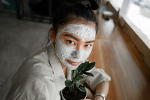 Young Asian Girl With A Clay Mask On Her Face Hugs A Flower Pot, The Concept Of Natural Products Lying In The Base Of The Mask