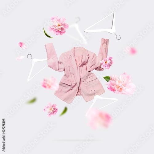 Creative Spring clothing concept. Womens fashionable flying pink blazer flowers peonies white wooden hanger on gray background. Female fashion, stylish fabric cotton jacket. Sale, springtime discounts © olgaarkhipenko