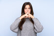Leinwandbild Motiv Teenager Brazilian girl over isolated blue background showing a sign of silence gesture