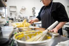 Female Baker Filling Tins With Batter In Commercial Bakery Kitchen