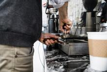 Close Up Male Barista Using Tamper At Espresso Machine In Cafe