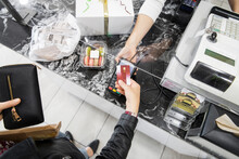 Female Customer Paying With Smart Credit Card At Bakery Counter