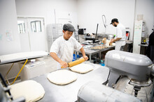 Male Baker Rolling Pastry Dough With Rolling Pin In Bakery Kitchen