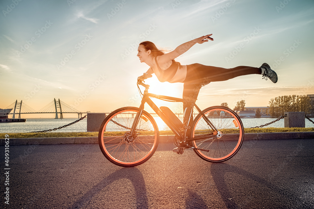 Fototapeta Athletic girl performing acrobatic riding on electric bike