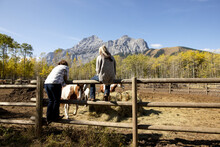 Female Ranchers Watching Horse Graze In Sunny Mountain Ranch Paddock