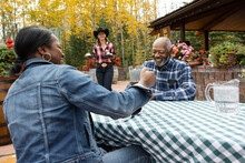 Happy Senior Couple Drinking Beer At Restaurant Patio Table