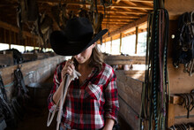 Young Female Rancher With Lasso Rope In Horse Stable
