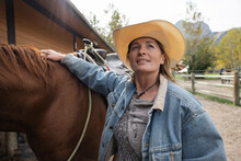 Beautiful Mature Woman In Cowboy Hat Horseback Riding On Ranch
