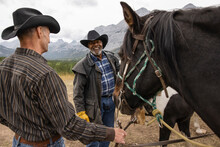 Happy Senior Male Friends In Cowboy Hats Horseback Riding In Mountains