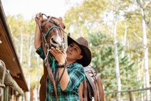 Female Rancher Harnessing Horse On Ranch