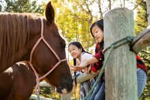 Happy Sisters Petting Horses At Ranch Paddock Fence