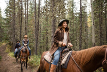 Happy Young Woman Horseback Riding With Friends On Trail In Woods