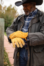 Senior Male Rancher Putting On Yellow Working Gloves