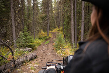 Female Rancher Riding Quad Bike On Rugged Trail In Woods