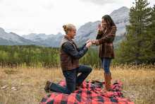 Young Man Proposing Marriage To Girlfriend On Scenic Mountain Hill