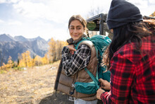 Mother Helping Daughter With Hiking Backpack In Autumn Mountains