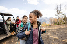 Teenage Girls Preparing For Hike With M Others On Autumn Mountain
