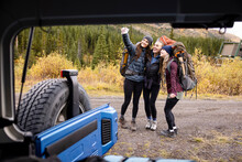 Happy Young Women Friends With Hiking Backpacks Taking Selfie At Jeep