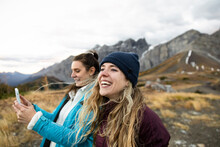 Happy Young Women Friends Hiking In Remote Mountains