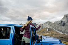 Young Woman With Smart Phone At Jeep In Remote Mountains