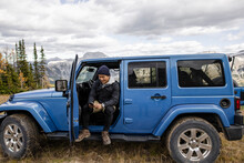 Man Using Smart Phone In Blue Jeep In Remote Mountains