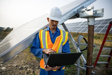 Technician Working On Laptop In Solar Farm