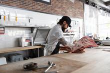 Butcher Chopping Up Meat Carcass