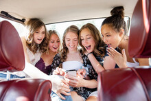 Surprised Teenage Girl Friends Using Smart Phone In Back Seat Of Car