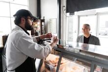 Customer Making Selection From Meat Counter In Butcher's Shop