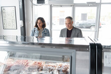 Customers Looking At Meat Counter In Butcher's Shop