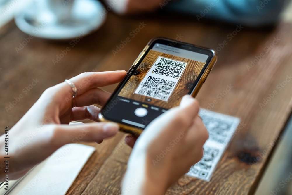 Fototapeta Young woman hands using the smart phone to scan the qr code to select food menu in the restaurant.