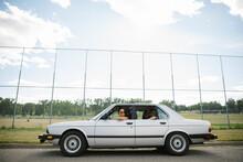 Teenage Girl Friends In Car Parked Outside High School Baseball Field
