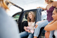 Carefree Teenage Girl Playing Ukulele With Friends At Pickup Truck