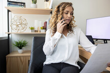 Corporate Businesswoman Talking On Smart Phone At Office Desk