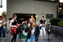 Teenage Girl Singing Into Microphone With Friends In Driveway