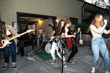 Teenage Girl Friends Playing Music As Rock Band In House Driveway