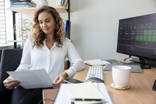 Corporate Businesswoman Reviewing Paperwork At Office Desk