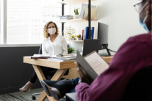 Business People In Face Masks Talking At Distance In Office