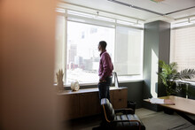 Thoughtful Young Businessman Looking Out Highrise Office Window
