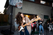 Teenage Girl Playing Electric Guitar With Friends In House Driveway