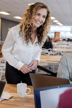Happy Businesswoman Talking With Colleagues In Office Meeting