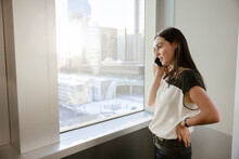 Young Businesswoman Talking On Smart Phone At Highrise Office Window