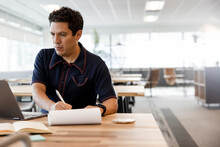 Focused Businessman Taking Notes At Laptop In Coworking Space Office