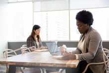 Businesswomen Working At Table In Coworking Space Office