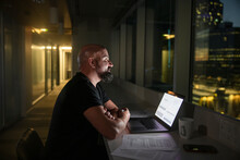 Businessman Working Late At Laptop In Office Window