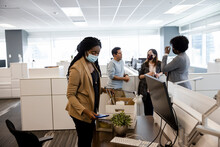 New Hire Businesswoman In Face Mask Unpacking Box In Office Cubicle