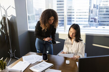 Businesswomen Discussing Paperwork In Highrise Office