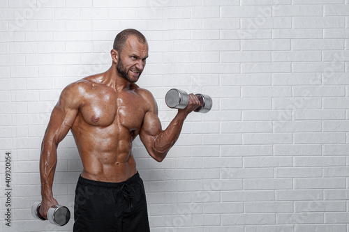 Bodybuilder doing exercises for biceps with a dumbbells against brick wall Fototapete