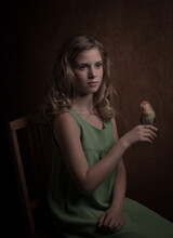 Girl Sitting In Vintage Green Dress Holding Her Colorful Lovebird (Apagornis) On Her Finger In Classic Painterly Style