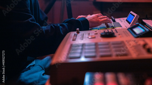 Fotografiet The hands of an artist creating music with his drum machines under red light